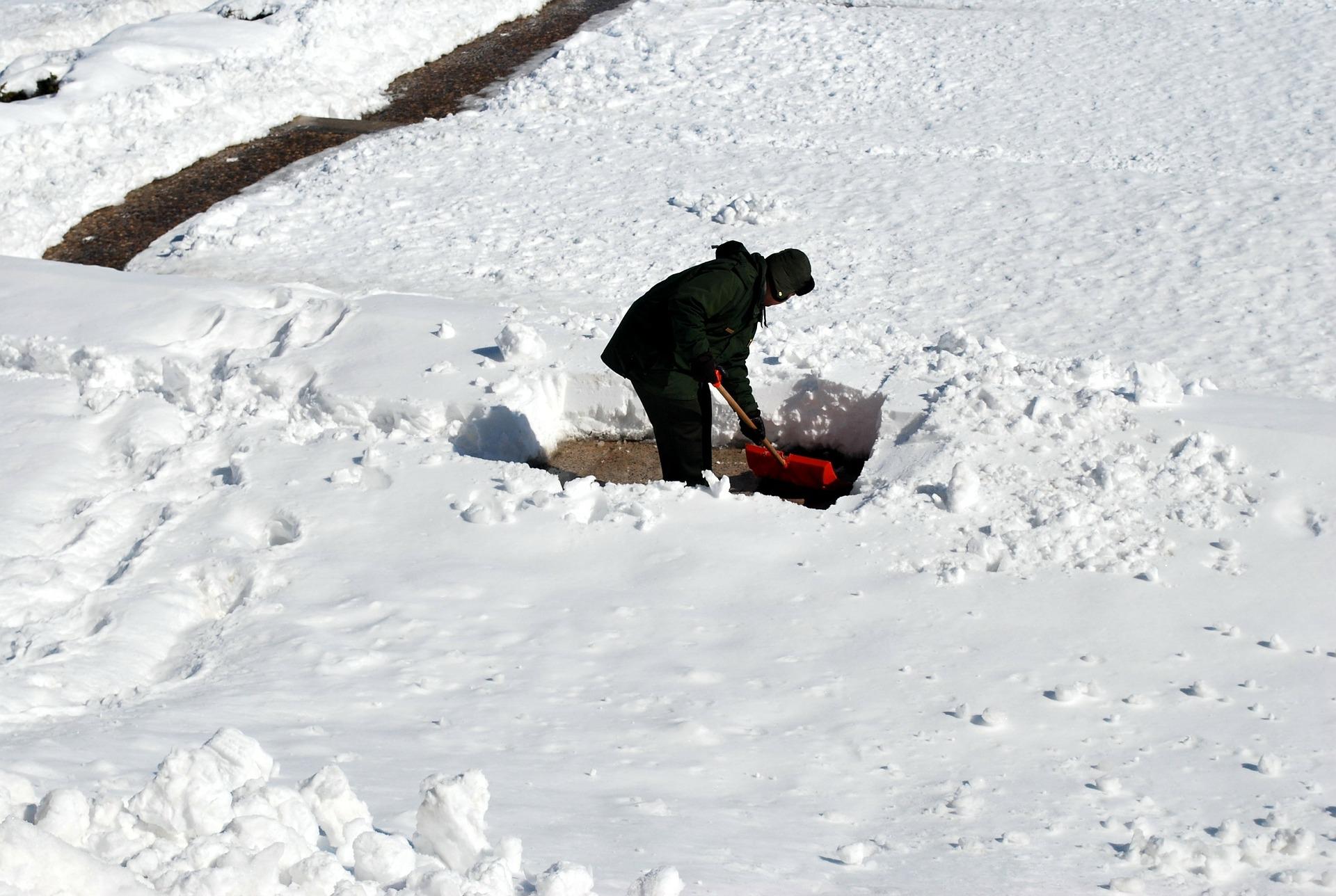 Skotta snö med skyffel.