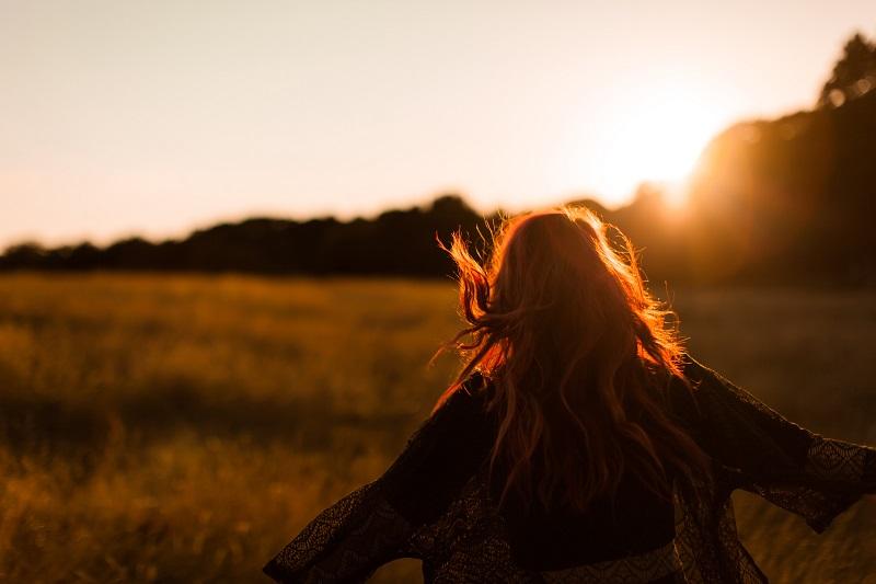 Kvinna blickar upp mot solen.